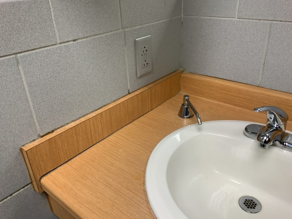 Tired sink area with dirty grout and caulking in dealership bathroom